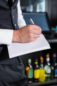 Il barista sta scrivendo un ordine nel bar
