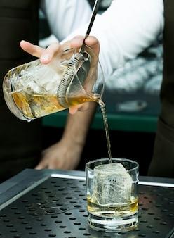 Il barista versa da bere in un bicchiere con molto ghiaccio