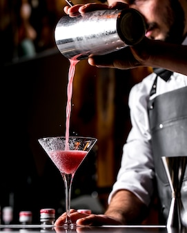 Il barista versa il cocktail dallo shaker al bicchiere da martini