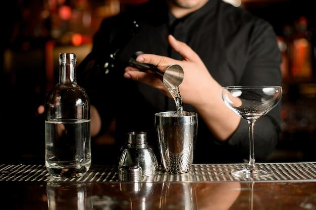 Il barista versa un alcool dal jigger di misurazione dell'acciaio