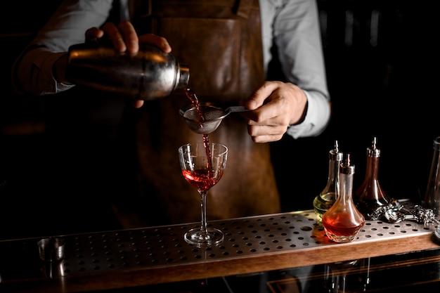Il barista versa una bevanda alcolica rossa dall'agitatore d'acciaio attraverso il setaccio