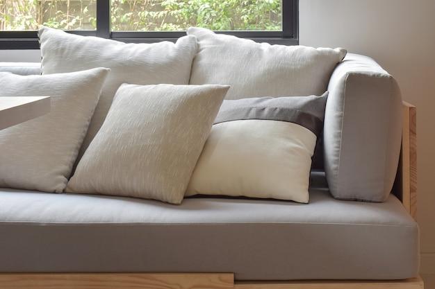 Il beige varia i cuscini di varie dimensioni su un comodo divano grigio chiaro