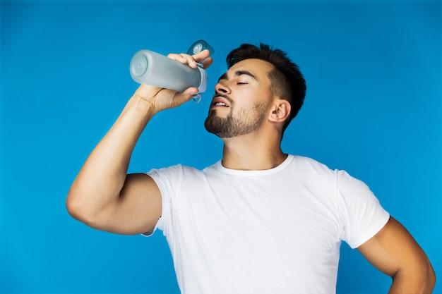 Il bel ragazzo assetato sta bevendo dalla bottiglia dello sport