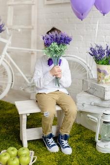 Il bel ragazzo con un'acconciatura e un mazzo di fiori blu