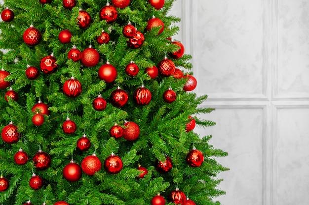 Il bello albero di natale con le bagattelle rosse si chiude su