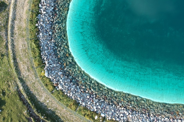 Il bello chiaro lago blu in un campo verde ha sparato da sopra