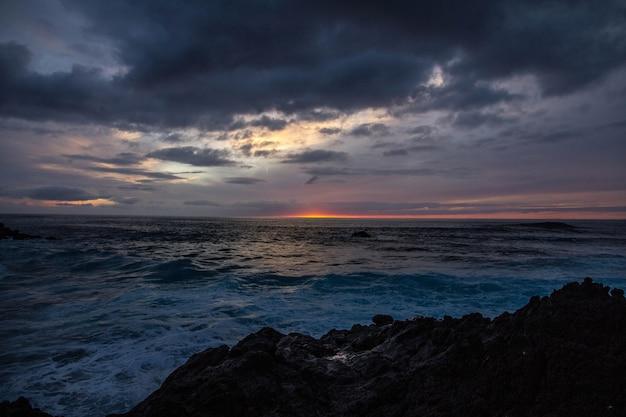 Il bello colpo del mare ondeggia vicino alle rocce sotto un cielo nuvoloso al tramonto