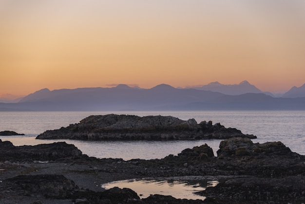 Il bello colpo delle scogliere rocciose si avvicina al mare sotto un cielo rosa
