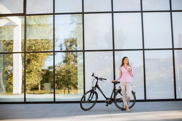 Il bello giovane ciclista femminile beve il caffè caldo da una tazza dalla bicicletta elettrica nell'ambiente urbano