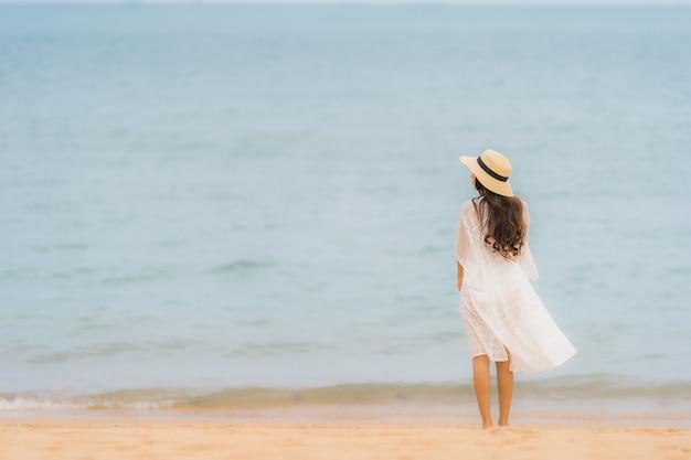 Il bello giovane giovane sorriso asiatico della donna del ritratto felice si rilassa sull'oceano del mare della spiaggia