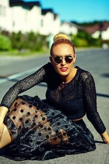 Il bello giovane modello biondo sorridente sexy alla moda divertente della donna in pantaloni a vita bassa del nero dell'estate copre la seduta nella via
