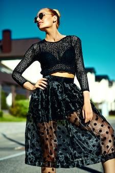 Il bello giovane modello biondo sorridente sexy alla moda divertente della donna in pantaloni a vita bassa del nero dell'estate copre nella via