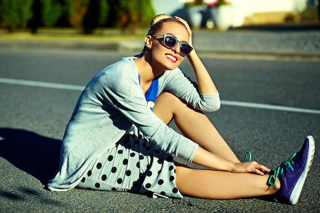 Il bello giovane modello biondo sorridente sexy alla moda divertente della donna in pantaloni a vita bassa dell'estate copre nella via