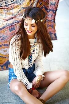 Il bello giovane modello sorridente sexy alla moda divertente della donna del hippie in pantaloni a vita bassa bianchi dell'estate copre la posa nella via