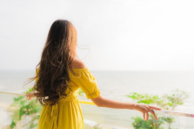 Il bello giovane sorriso asiatico della donna del ritratto felice e si rilassa al balcone all'aperto con la spiaggia e l'oce del mare