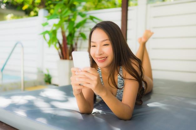 Il bello giovane sorriso asiatico della donna del ritratto felice si rilassa con il telefono cellulare intorno alla piscina