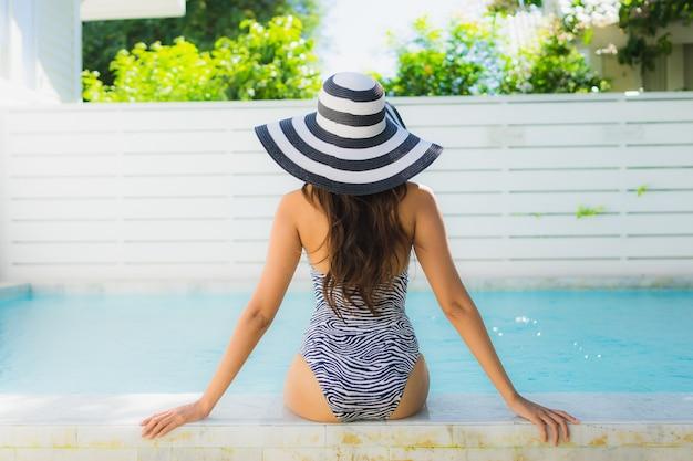 Il bello giovane sorriso asiatico della donna del ritratto felice si rilassa intorno alla piscina nella località di soggiorno dell'hotel per svago