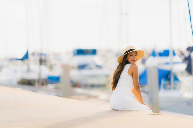 Il bello giovane sorriso asiatico di svago della donna del ritratto felice si rilassa intorno al porto dell'yacht