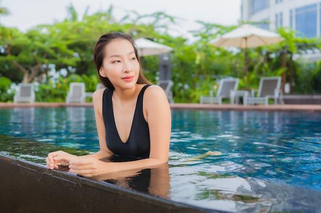 Il bello giovane svago asiatico della donna del ritratto si rilassa il sorriso intorno alla piscina all'aperto per la vacanza