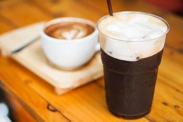 Il bello iced americano o il caffè nero con la schiuma forma i chicchi di caffè freschi