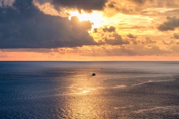Il bello mare dorato con luce solare splende al tramonto