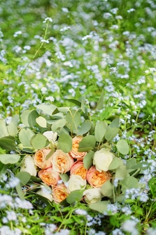 Il bello mazzo di nozze sta trovandosi nell'erba. gli anelli di fidanzamento sono sui fiori.