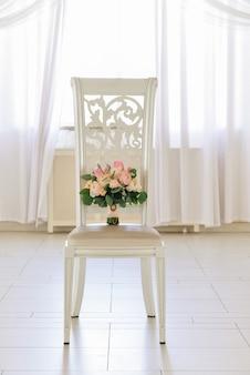 Il bello mazzo di nozze tenero delle rose è sulla sedia