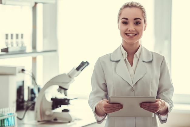 Il bello medico femminile sta usando una compressa digitale.