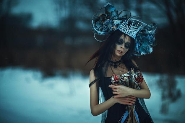 Il bello modello che porta il vestito nero sta posando su una neve