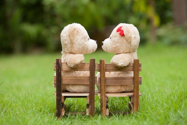 Il bello orsacchiotto di bacio si siede sulla sedia di legno