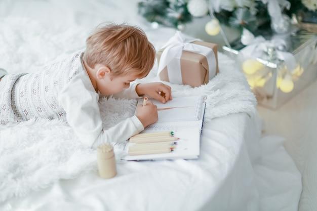 Il bello piccolo neonato in pigiama con le stelle celebra il natale.