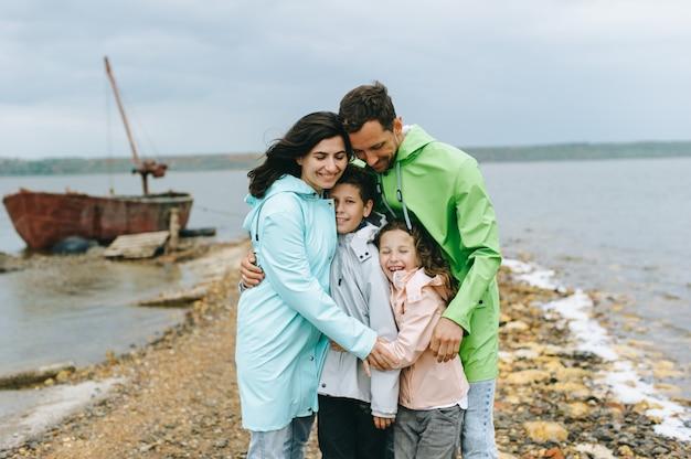 Il bello ritratto della famiglia si è vestito in impermeabile variopinto vicino al lago