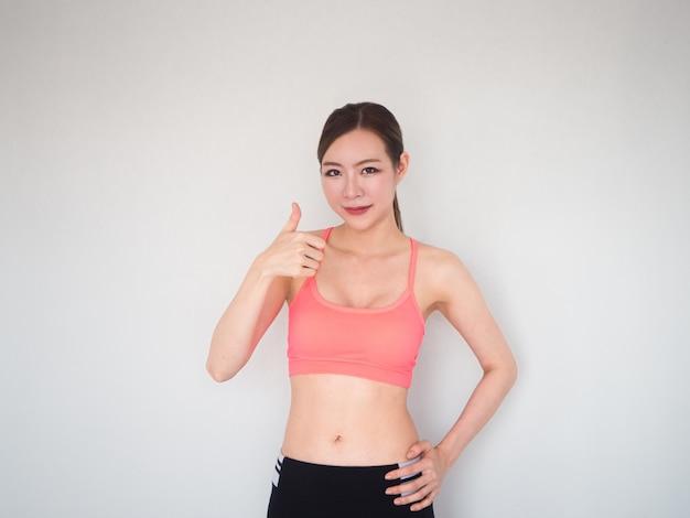 Il bello segno della tenuta della donna di forma fisica su aumenta, donna di sport su fondo bianco