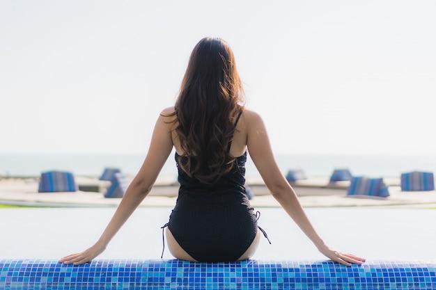 Il bello sorriso felice della giovane donna asiatica e si rilassa nella piscina