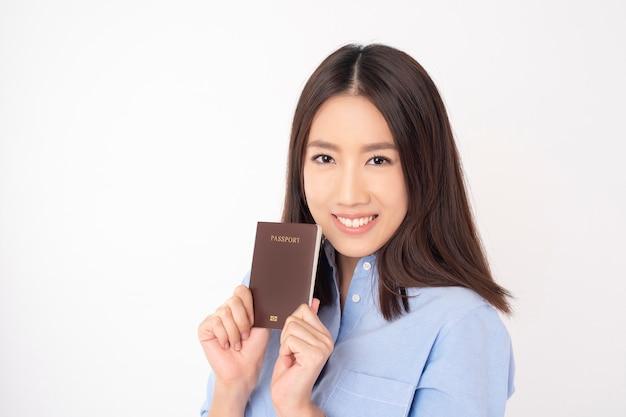 Il bello turista asiatico della donna sta tenendo il passaporto sulla parete bianca