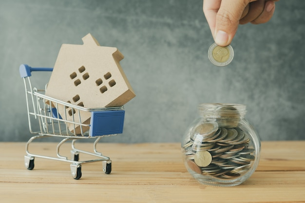 Il bene immobile e l'acquisto e la vendita del concetto domestico, mano hanno messo la moneta dei soldi in barattolo e modello della casa in carrello