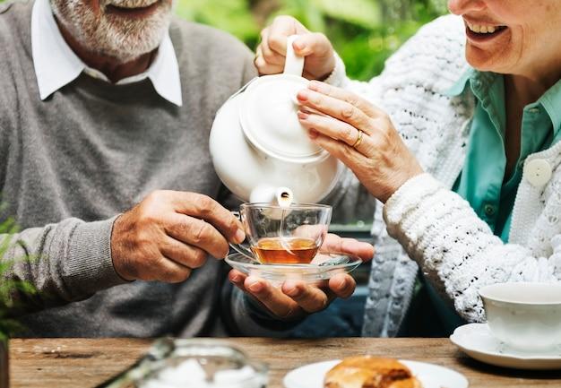 Il bere del tean di pomeriggio delle coppie senior si rilassa il concetto