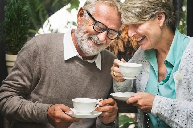 Il bere di tean di pomeriggio delle coppie senior si rilassa il concetto