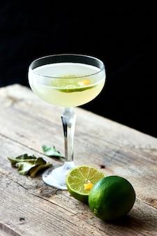 Il bicchiere di cocktail alcolici daiquiri è costituito da rum sulle foglie di lime, lo sciroppo di fiori di sambuco si trova sul tavolo di legno su sfondo nero
