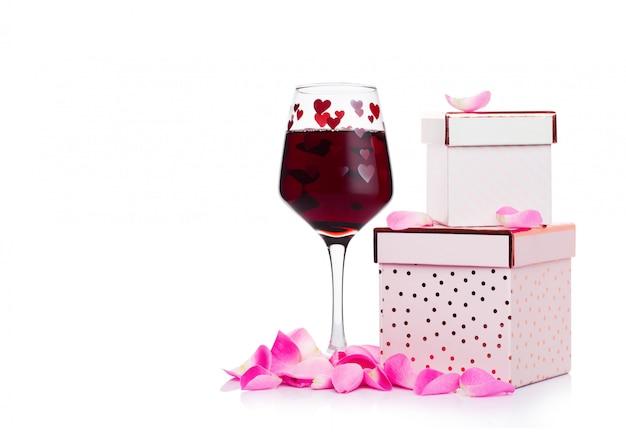Il bicchiere di vino rosso con cuore e il contenitore di regalo rosa ed è aumentato per il san valentino su fondo bianco