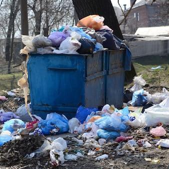 Il bidone della spazzatura è pieno di rifiuti e rifiuti. rimozione intempestiva di rifiuti in aree popolate