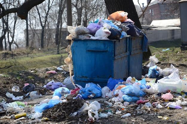 Il bidone della spazzatura è pieno di rifiuti e rifiuti.