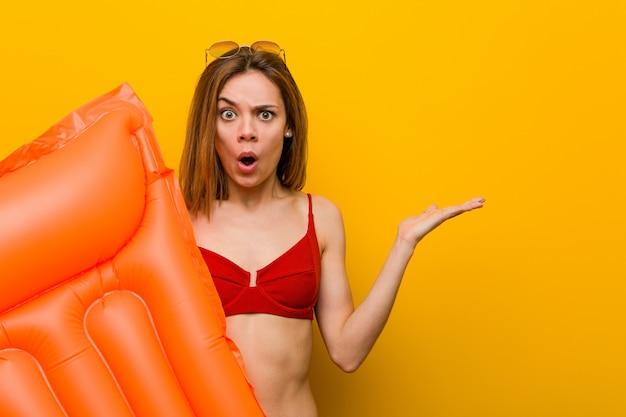 Il bikini d'uso della giovane donna, tenente un letto del materasso di aria ha impressionato lo spazio della copia della tenuta sulla palma.
