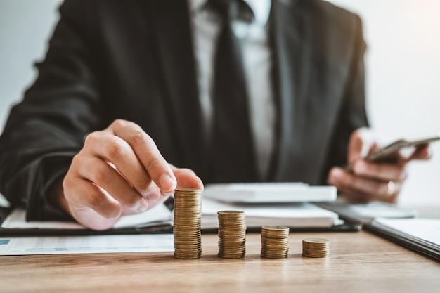 Il bilancio economico di costo calcolatore di contabilità dell'uomo di affari che mette la fila e la moneta scrive la finanza, l'investimento e il concetto di risparmio