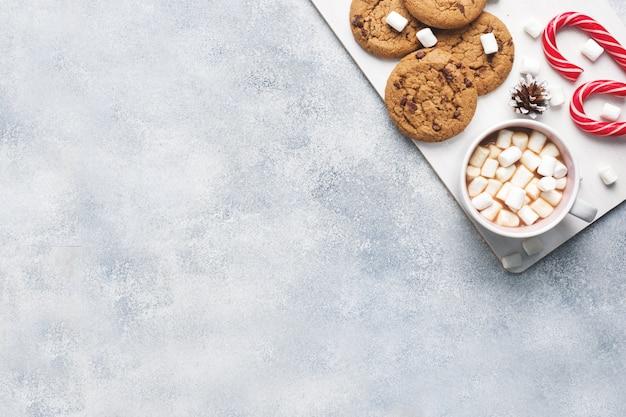 Il biscotto con gocce di cioccolato, la caramella di canna di natale cup cacao e marshmallow coni decorazioni su un grigio. cornice di copyspace.