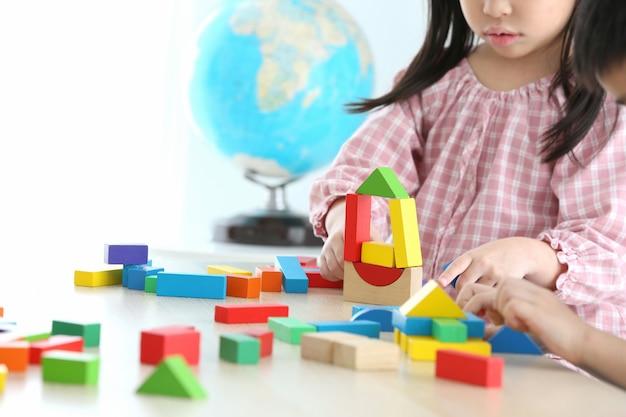 Il blocco di configurazione asiatico dello studente prescolare gioca a casa o all'asilo nido. bambino allegro che gioca con i cubi di colore. giocattoli educativi per bambini in età prescolare e all'asilo.