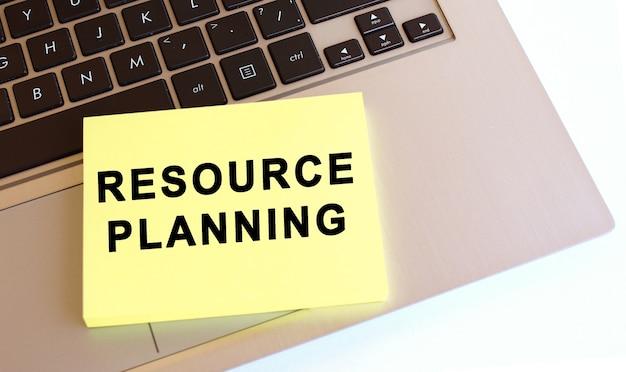 Il blocco note con il testo è sulla tastiera del laptop. spazio di lavoro minimo. concetto di affari.