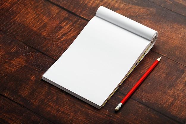 Il blocco note con la matita rossa su un fondo di legno marrone della tavola, per istruzione, scrive gli obiettivi e le azioni