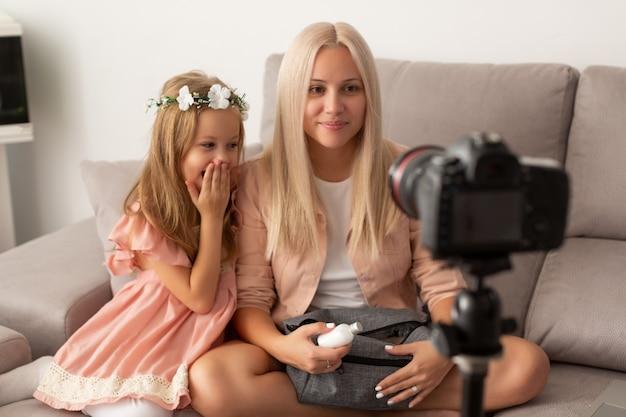 Il blogger allegro della figlia e della madre sta mostrando i prodotti dei cosmetici