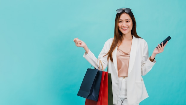Il blogger asiatico delle belle donne sta usando lo smartphone che compera online con un sacchetto della spesa.